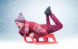 Funny man in red sweater and cap on sled in the snow, concept winter fun Royalty Free Stock Photography