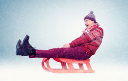 Funny man in red sweater and cap on sled in the snow, concept winter fun Stock Images