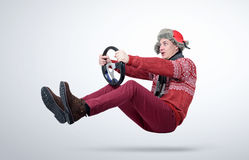Funny man in red sweater, scarf and hat, driving car with the steering wheel Stock Image