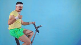 Funny man from the 80`s with a mustache on exercise bike on a blue background, shows thumb up. Funny young man from the 80`s with a mustache on exercise bike on stock video