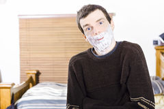Funny man with shaving cream beard. Male skincare. Funny man standing indoors at home smiling with shaving cream foam beard. Male skincare and grooming concept Royalty Free Stock Images