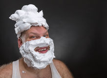 Funny man with shaving foam covered face. Bizarre smiling man with shaving foam on his face and on his head over grey background Stock Image
