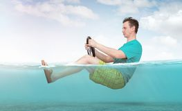 Funny man in shorts, T-shirt and sandals rides on the sea with a car steering wheel. Concept of going on vacation stock images