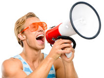 Funny man shouting in megaphone isolated on white background. Funny man shouting in megaphone wearing sunglasses Stock Image