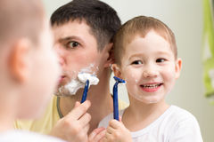Funny man and son little child shave looking at Stock Photo