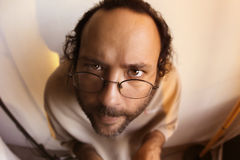 Funny man staring at you. Bearded man in glasses making funny face Stock Image