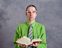 Funny man with statute book and pink glasses. Funny man in green shirt and necktie with statute book and pink glasses Stock Photos