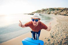 Funny man with suitcase showing thumbs up against the blue ocean. Travel concept. Funny man with suitcase showing thumbs up against the blue ocean. Travel Royalty Free Stock Photography
