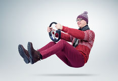 Funny man in sweater, scarf and hat, driving car with the steering wheel Royalty Free Stock Photography