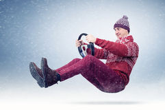 Funny man in sweater, scarf and hat, driving car with the steering wheel. Winter, snow, blizzard Royalty Free Stock Photo