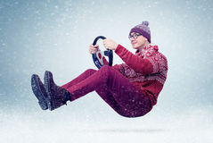 Funny man in sweater, scarf and hat, driving car with the steering wheel. Winter, snow, blizzard Stock Photo