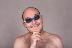 Funny man in swimming goggles daydreaming and looking at you Royalty Free Stock Images