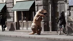 Funny man in t rex costume in crowd of people walking on city sidewalk. Cold sunny spring or autumn day, lots of cars. Slow motion stock video footage