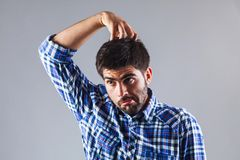 Funny man thinking while scratchin his head Royalty Free Stock Photos