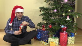 Funny man unfold chocolate Christmas Santa and lick lips. Funny gourmand man unfold chocolate Christmas Santa and lick lips near fir tree with toys and gifts stock video footage
