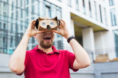Funny man using cardboard virtual reality goggle outdoors Royalty Free Stock Images