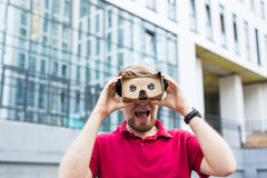 Funny man using cardboard virtual reality goggle outdoors Stock Images