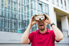 Funny man using cardboard virtual reality goggle outdoors Stock Photography