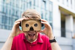 Funny man using cardboard virtual reality goggle outdoors Royalty Free Stock Photo