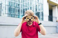 Funny man using cardboard virtual reality goggle outdoors Stock Photo