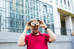 Funny man using cardboard virtual reality goggle outdoors Royalty Free Stock Photos