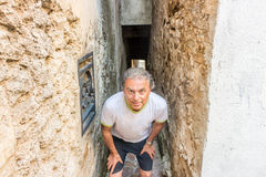 Funny man waiting in narrow alley Royalty Free Stock Photo