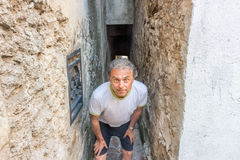 Funny man waiting in narrow alley Stock Photos
