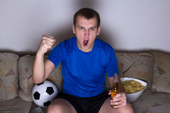 Funny man watching football on tv. And celebrating goal in living room Royalty Free Stock Photography