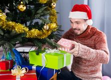Man wearing Santa puts gifts under the Christmas tree Royalty Free Stock Images