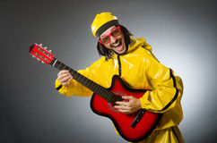 Funny man wearing yellow suit and playing guitar Royalty Free Stock Photography