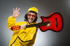 Funny man wearing yellow suit and playing guitar Stock Images