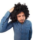 Funny man with the wig while scratching head Royalty Free Stock Photography