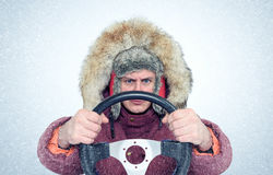Funny Man in winter clothes with a steering wheel, snow blizzard. Concept car driver. Stock Photo