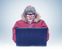 Funny man in winter clothing in front of a laptop, cold, steam from the mouth. Hacker in a fur hat concept Stock Photography