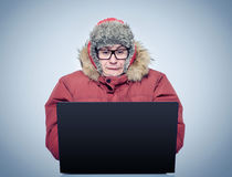 Funny man in winter clothing in front of a laptop. Russian hacker concept Stock Photography