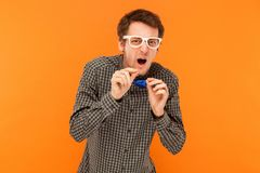 Funny manager looking at camera with disgust look. Indoor, orange background Stock Photos