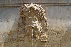 Funny mascaron face on fountain Stock Photo