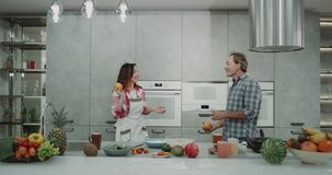 Funny mature couple juggling together with oranges in a modern gray kitchen , while making breakfast. 4k stock video footage