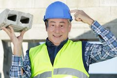 Funny mature male engineer touching helmet. Funny mature male engineer touching his helmet royalty free stock photography