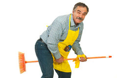 Funny mature man riding broom. Funny cleaner mature man riding broom isolated on white background Stock Photo