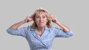 Funny mature woman on grey background. Middle-aged caucasian woman making funny face grimace. Woman is fooling stock video footage