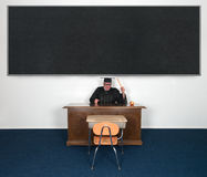 Funny Mean Angry Teacher Chalkboard YOUR TEXT HERE. Funny mean angry school teacher or college professor in the classroom. There is a desk and a large, big Stock Photos