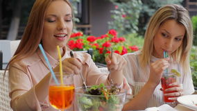 Funny meeting with the girlfriend. Women on the terrace of a cozy cafe rejoices meeting stock video footage