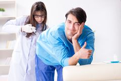 The funny man getting ready for buttocks syringe shot. Funny men getting ready for buttocks syringe shot Stock Image