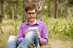 Funny men with glasses doing homework at the park Stock Images