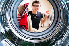 Funny men loading clothes to washing machine Royalty Free Stock Photography