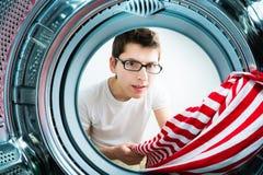 Funny men loading clothes to washing machine Stock Photo