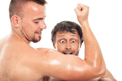 Funny men looking at biceps Royalty Free Stock Images