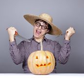 Funny men try to eat a pumpkin. Stock Photo