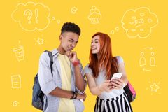 Excited girl holding a smartphone and showing messages to her calm friend. Funny message. Cheerful pretty student smiling and showing a funny message to her Royalty Free Stock Photos